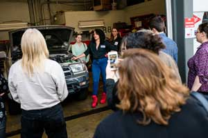 Lehigh alumni and students gather around a car engine during an auto clinic hosted by Patrice Banks '02 at her full-service garage in Upper Darby, PA