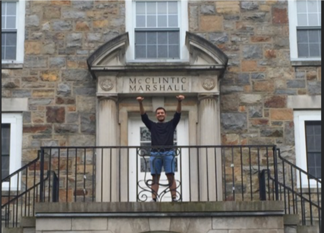 JP Villamar poses with arms in the air in front of his freshman year dorm at Lehigh University