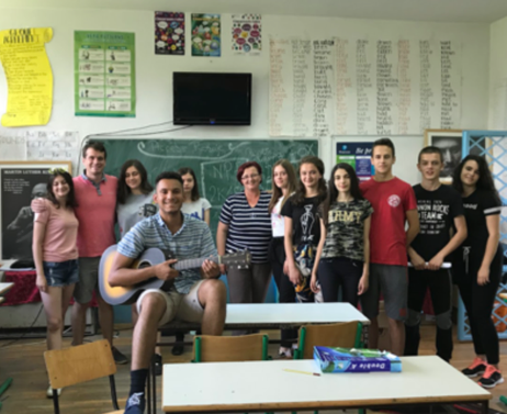 JP Villamar poses with high school students in a classroom in Montenegro during his internship.