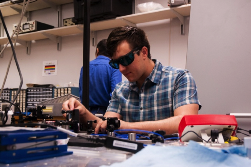 A male graduate student in Prof. Ariel Sommer's physics lab works on an experiment to study quantum transport using ultra-cold atomic gases