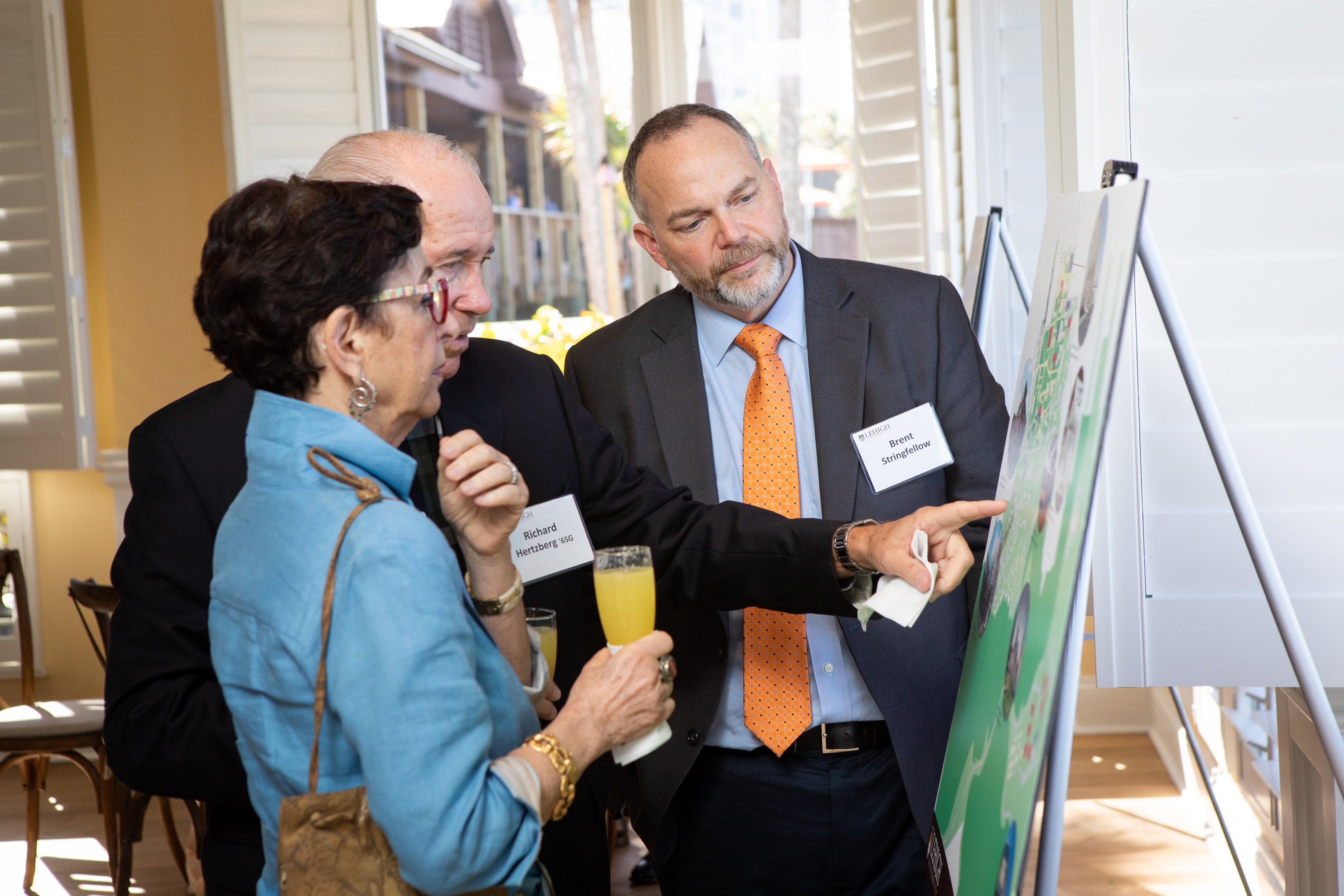 Linda and Richard Hertzberg '65G look over campus plans with Brent Stringfellow, associate vice president for facilities services and university architect, at the Tower Society event in Naples, Florida.