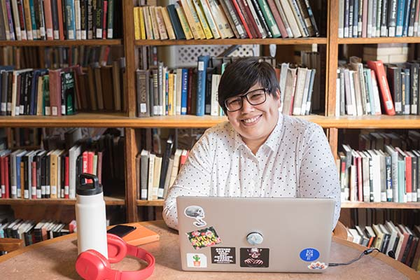 Katherine Tarazona seated at a table in a library in front of a bookshelf working on her laptop