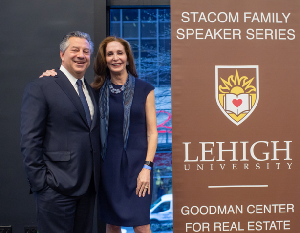 Marc Holliday '88 stands with Tara Stacom '80 in front of a Lehigh University banner